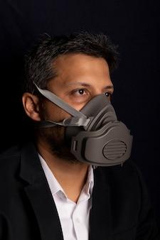 Jong knap met industrieel masker om de verspreiding van besmettelijke virussen of chemische gassen te voorkomen