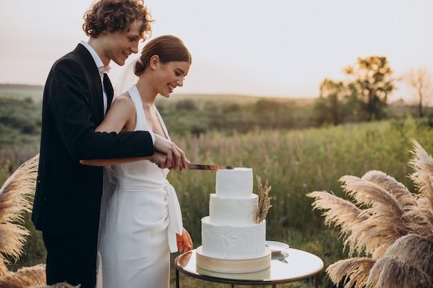 Jong koppel aan het snijden van hun bruidstaart Gratis Foto