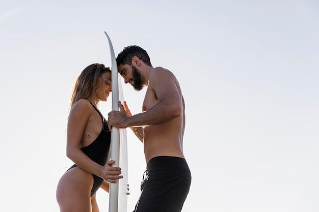 Jong koppel aanraken van surfplank met voorhoofden