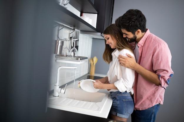 Jong koppel afwassen in de keuken terwijl ze knuffelen en plezier hebben