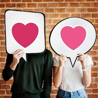 Jong koppel bedrijf tekstballonnen met hart pictogrammen