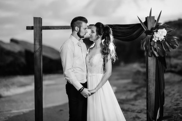 Jong koppel bruidegom en bruid met een boeket in de avond op het strand in de buurt van de huwelijksboog