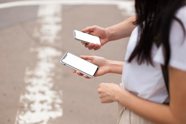 Jong koppel buitenshuis doorbladeren van mobiele telefoons