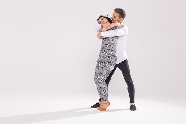 Jong koppel dansen sociale latin dans bachata, merengue, salsa. twee elegantie pose op witte achtergrond.