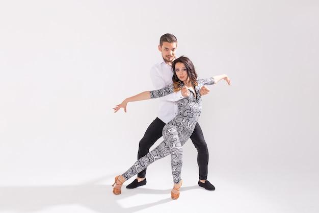 Jong koppel dansen sociale latin dans bachata, merengue, salsa. twee elegantie poseren op een witte achtergrond met kopie ruimte