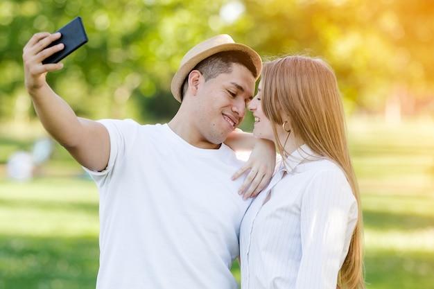 Jong koppel dat een selfie op hun mobiel in het park neemt