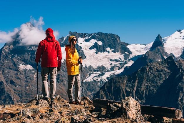 Jong koppel doet nordic walking in de bergen, achteraanzicht. een actief stel houdt zich bezig met wandelen. een jong stel houdt zich bezig met het volgen. trekking en nordic walking. hiking. ruimte kopiëren