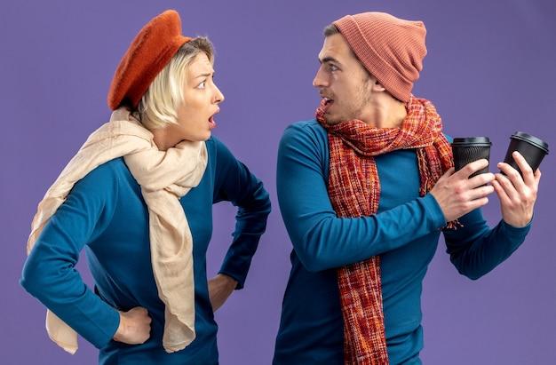 Jong koppel dragen hoed met sjaal op valentijnsdag boos meisje kijken naar man met kopje koffie geïsoleerd op blauwe achtergrond