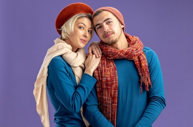 Jong koppel dragen hoed met sjaal op valentijnsdag lachend meisje handen op de schouder van de man geïsoleerd op blauwe achtergrond
