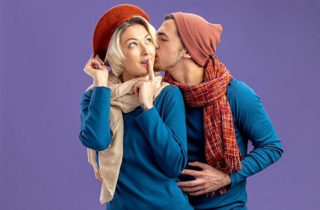 Jong koppel dragen hoed met sjaal op valentijnsdag man zoenen meisje wang geïsoleerd op blauwe achtergrond