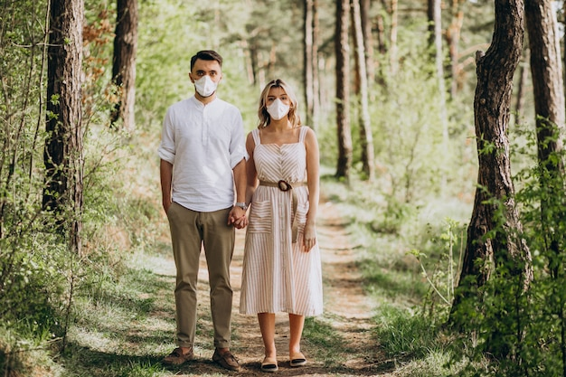 Jong koppel dragen maskers samen in het bos