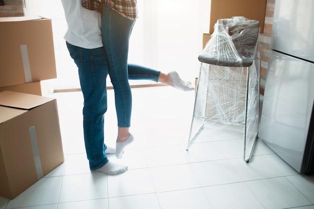 Jong koppel eerste keer huiseigenaren vieren bewegende dag concept, man man tillen bedrijf vrouw staande in de buurt van dozen in nieuw eigen huis appartement, verhuizing en familie hypotheek.