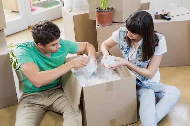 Jong koppel elkaar bijstaan tijdens het uitpakken van kartonnen dozen in een nieuw huis