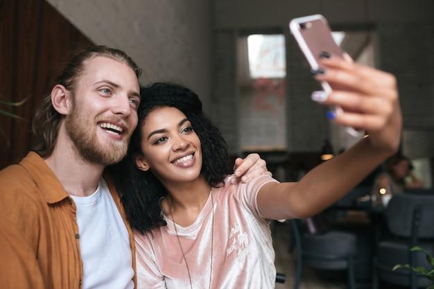 Jong koppel foto's maken op frontale mobiel camera in restaurant