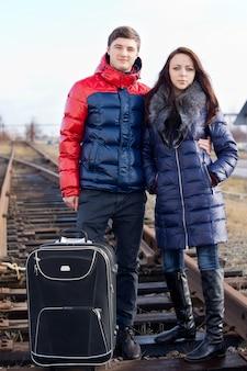 Jong koppel gaat op vakantie arm in arm met hun koffer in het midden van het spoor op de houten dwarsliggers wachten op de trein
