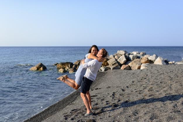 Jong koppel gek rond op de achtergrond van de zee. geschoten op het strand van santorini.