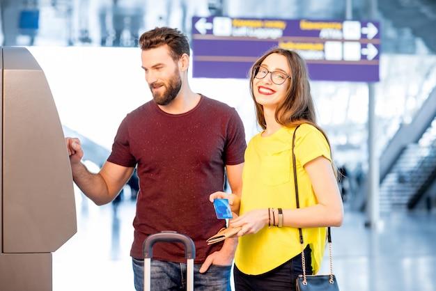 Jong koppel geld opnemen met behulp van atm op de luchthaven tijdens hun reis