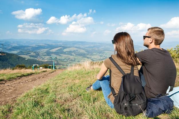 Jong koppel genieten van bergen landschap, zittend op de heuvel