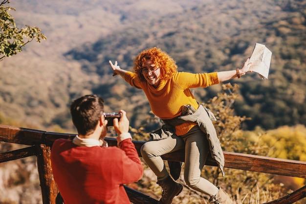 Jong koppel genieten van de natuur op een mooie zonnige herfstdag. vrouw zittend op hek.