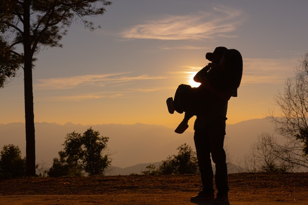 Jong koppel genieten van de zonsondergang in de bergen