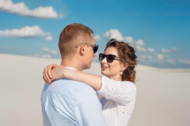 Jong koppel genieten van de zonsondergang in de duinen. romantische reiziger loopt in de woestijn. avontuurlijke reis levensstijl concept