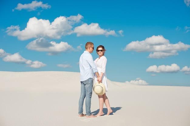 Jong koppel genieten van de zonsondergang in de duinen. romantische reiziger wandelingen in de woestijn. avontuurlijke reizen levensstijl concept