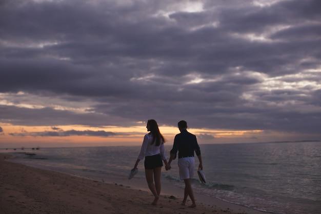 Jong koppel genieten van de zonsondergang op het strand