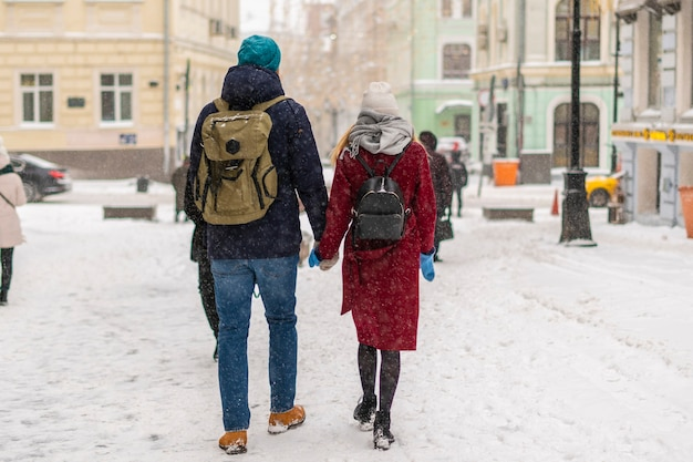 Jong koppel genieten van wandelen in de straten van de stad in het winterseizoen b
