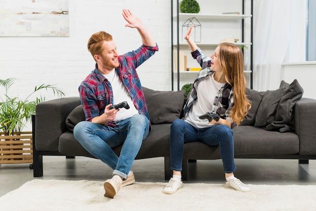 Jong koppel geven hoge vijf tijdens het spelen van het videogame in de woonkamer