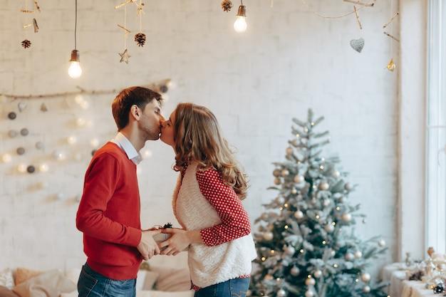 Jong koppel geven kerstcadeautjes aan elkaar