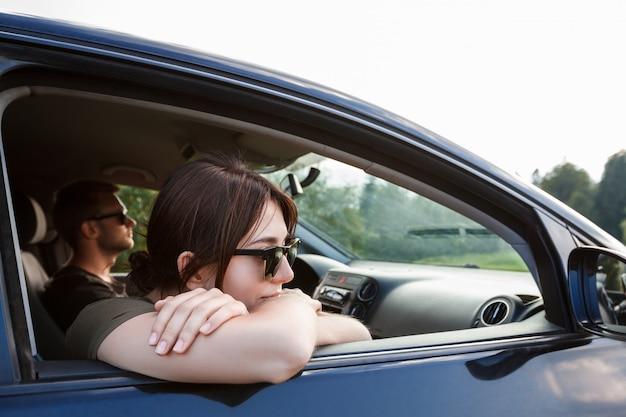 Jong koppel glimlachen, zitten in de auto, genieten van uitzicht op de bergen