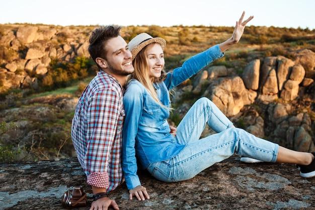 Jong koppel glimlachen, zittend op rots in canyon, genieten van uitzicht