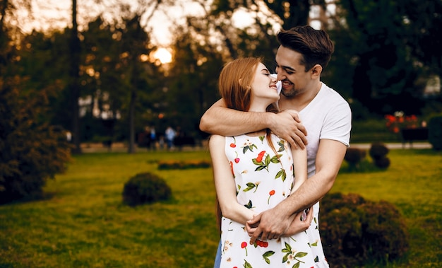 Jong koppel glimlachend en knuffelen elkaar en lachend buiten tegen zonsondergang
