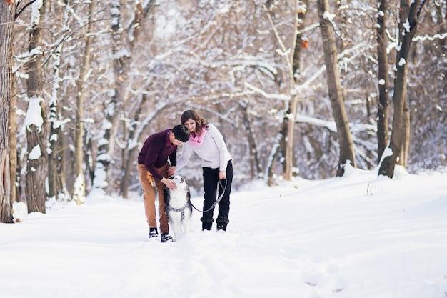 Jong koppel glimlachend en plezier in winter park met hun husky hond.