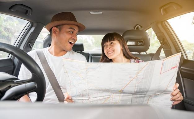 Jong koppel glimlachend met behulp van een kaart op een road trip voor richtingen zitten in een auto