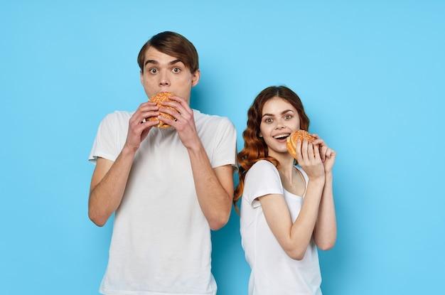 Jong koppel hamburgers in handen snack levensstijl blauwe achtergrond