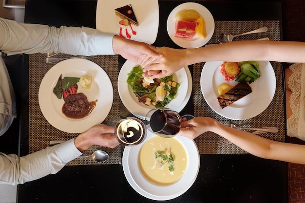 Jong koppel hand in hand en rammelende wijnglazen boven tafel met smakelijke gerechten
