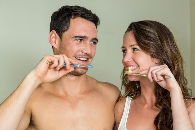 Jong koppel hun tanden thuis in de badkamer poetsen