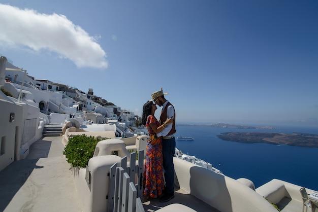 Jong koppel huwelijksreis op het meest romantische eiland santorini, griekenland. zonsondergang in de stad oia