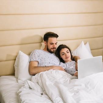 Jong koppel in bed met behulp van laptop