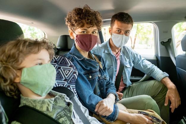 Jong koppel in beschermende maskers die naar je kijken terwijl ze in de auto zitten naast hun schattige zoontje tijdens de periode van covid19-epidemie