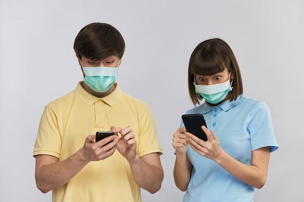 Jong koppel in beschermingsmaskers op zoek naar smartphones met grote verbaasde ogen