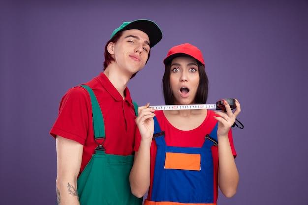 Jong koppel in bouwvakker uniform en cap zelfverzekerde man verrast meisje met tapemeter beide kijken naar camera geïsoleerd op paarse muur