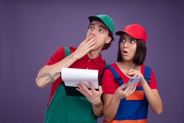Jong koppel in bouwvakker uniform en pet bezorgde man met potlood en klembord hand op mond verbaasd meisje met mobiele telefoon beide opzoeken geïsoleerd op paarse muur
