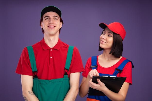 Jong koppel in bouwvakker uniform en pet blij meisje met potlood en klembord kijken naar man glimlachend man opzoeken geïsoleerd op paarse muur