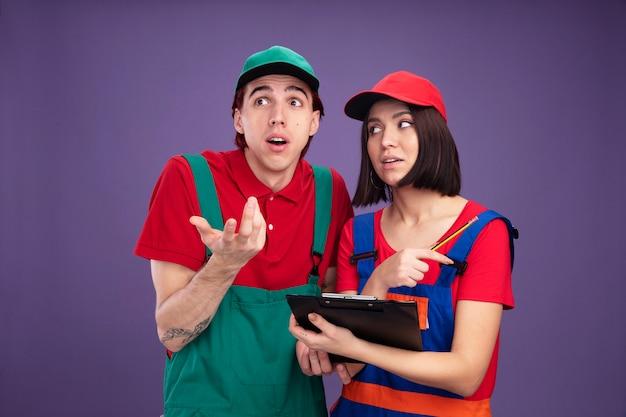 Jong koppel in bouwvakker uniform en pet geconcentreerd meisje met potlood en klembord kijken naar man clueless man weergegeven: lege hand kijken naar kant geïsoleerd op paarse muur