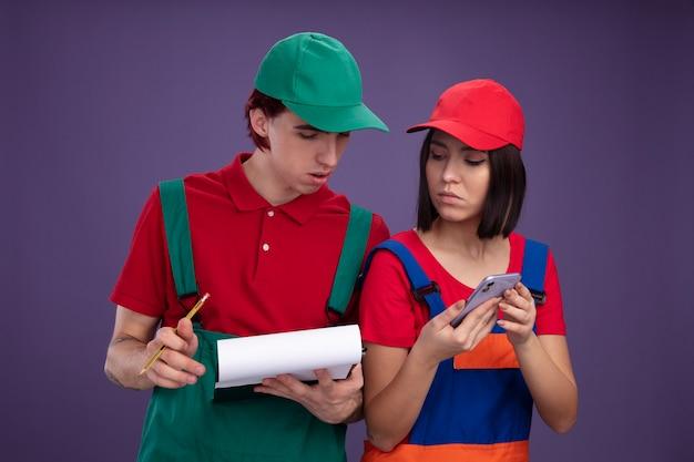 Jong koppel in bouwvakker uniform en pet geconcentreerde man met potlood en klembord serieus meisje met mobiele telefoon beide kijken naar klembord geïsoleerd op paarse muur