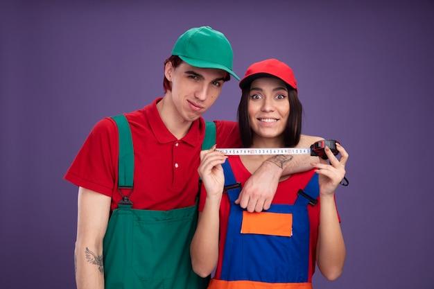 Jong koppel in bouwvakker uniform en pet kijken camera blij man houden arm rond de schouder van het meisje glimlachend meisje met tape meter geïsoleerd op paarse muur