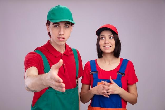 Jong koppel in bouwvakker uniform en pet onder de indruk man kijken camera doen groet gebaar opgewonden meisje handen bij elkaar houden kijken naar kant geïsoleerd op witte muur