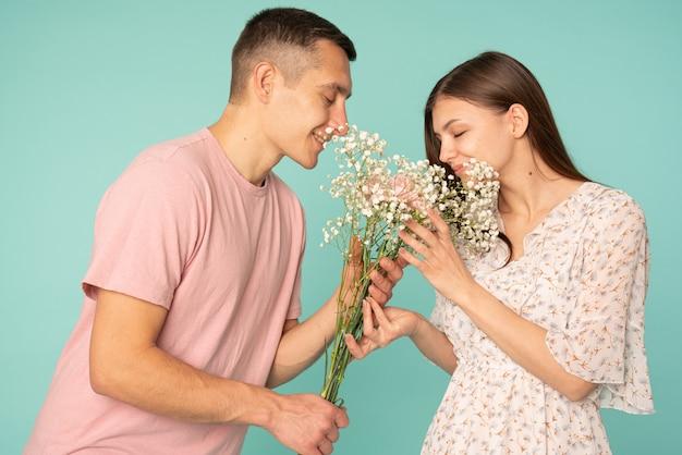 Jong koppel in casual kleding bij elkaar houden boeket en geurende bloemen met gesloten ogen